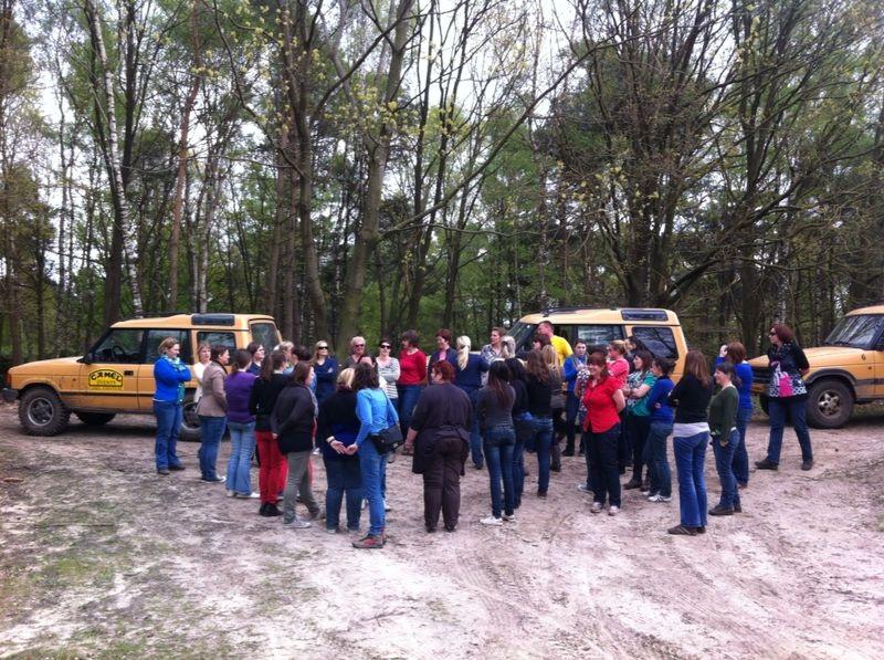Groep mensen luistert naar uitleg van instructeur met 4x4 Land Rovers op de achtergrond